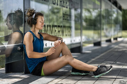 Young sportive woman wearing headphones and checking her smartwatch - STSF02187