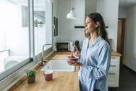 Young woman wearing pyjama in kitchen at home looking out of window - KIJF02528