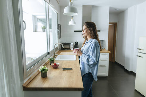 Young woman wearing pyjama in kitchen at home looking out of window - KIJF02531
