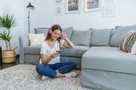 Smiling young woman sitting on floor in living room listening to music with cell phone - KIJF02543
