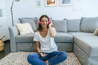 Happy young woman sitting on floor in living room listening to music with cell phone - KIJF02546
