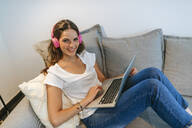 Portrait of smiling young woman on couch at home with headphones and laptop - KIJF02549