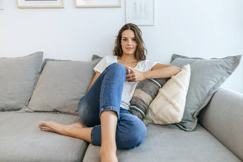 Portrait of young woman sitting on sofa with cell phone - KIJF02552