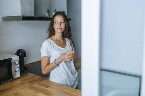 Young woman standing in the kitchen with glass of orange juice - KIJF02561