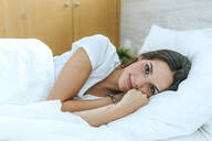 Portrait of young woman lying in bed at home - KIJF02570