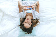 Top view of young woman lying in bed using cell phone - KIJF02579