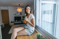 Smiling young woman sitting on kitchen counter with a drink - KIJF02582
