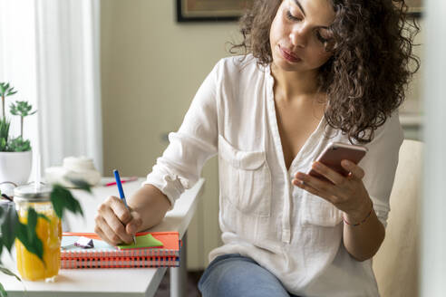 Young woman using cell phone and taking notes at desk at home - AFVF03724