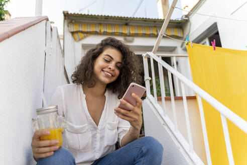 Smiling young woman sitting on stairs with cell and orange juice - AFVF03748