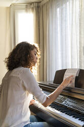 Woman playing piano at home - AFVF03775