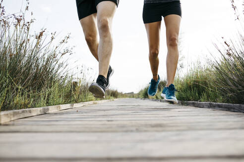 Young couple jogging on wooden walkway - JRFF03640