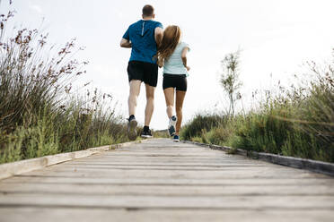 Rear view of young couple jogging on wooden walkway - JRFF03643
