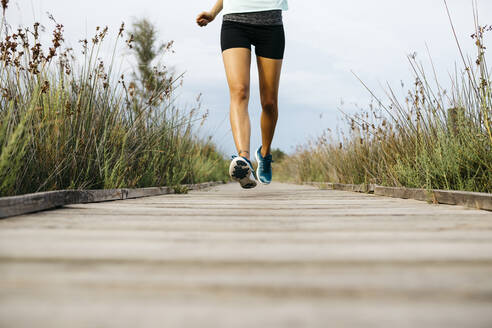 Female jogger running on wooden walkway - JRFF03646