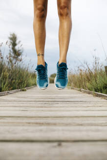 Feet of female jogger, jumping on a wooden walkway - JRFF03649