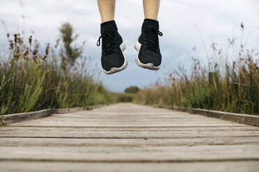 Black running shoes, male jogger jumping on a wooden walkway - JRFF03655