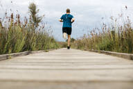 Rear view of a jogger running on a wooden walkway - JRFF03658