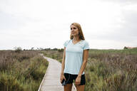 Female jogger with earphones and smartphone standing on a wooden walkway - JRFF03661