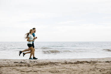 Young couple jogging on the beach - JRFF03670