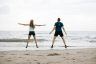 Young couple during training on the beach - JRFF03679