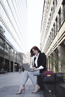 Businesswoman in the city, using laptop - EYAF00369