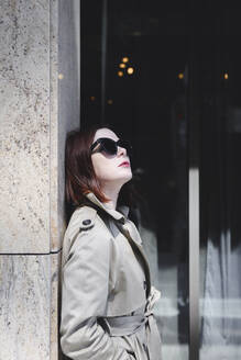 Portrait of a stylish woman with sunglasses and trenchcoat - EYAF00372