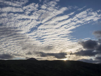 Low angle view of silhouette mountain against cloudy sky at sunset, Scotland, UK - HUSF00065