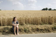 Young woman sitting barefoot at roadside in front of grain field - FLLF00270
