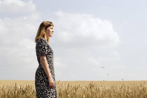 Deutschland,NRW,Ruhrgebiet,Stadt Essen,junge Frau mit Blumenkleid in einem Getreidefeld - FLLF00273