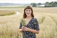 Portrait of smiling young woman with bunch of chamomile flower standing in front of grain field - FLLF00276