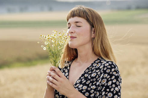 Smiling young woman with eyes closed smelling bunch of chamomile flower in nature - FLLF00279