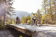 Mother and daughter riding e-mountain bikes in the mountains - FKF03531