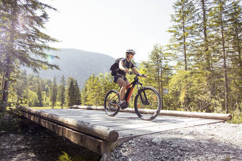 Woman riding  e-mountain bike in the mountains - FKF03534