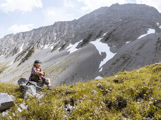 Girl having a break during a hike in the mountains - FKF03543