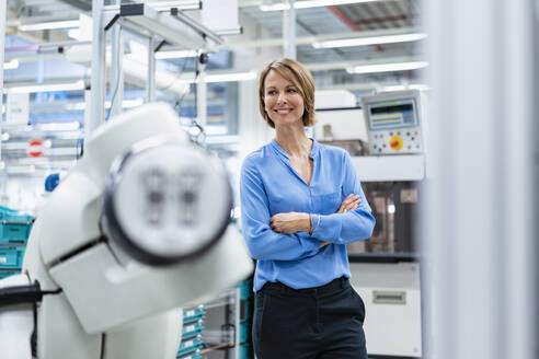 Portrait of businesswoman at assembly robot in a factory - DIGF07812