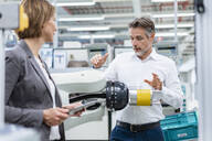 Businesswoman and man talking at assembly robot in a factory - DIGF07824