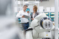 Businesswoman and man with tablet talking at assembly robot in a factory - DIGF07833