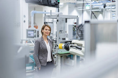 Portrait of a confident businesswoman in a modern factory - DIGF07839