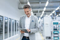 Smiling businessman using tablet in a modern factory - DIGF07857