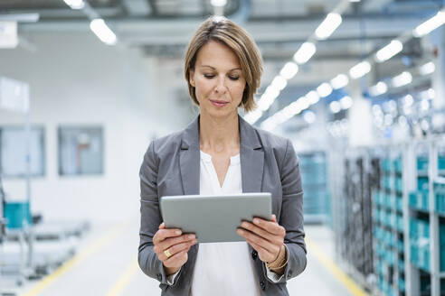 Businesswoman using tablet in a modern factory - DIGF07866