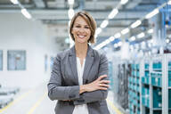 Portrait of a smiling businesswoman in a modern factory - DIGF07869