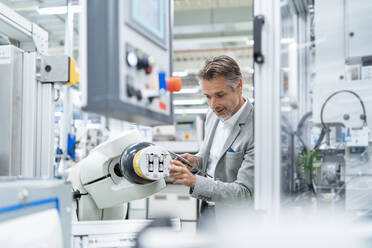 Businessman with tablet at assembly robot in a factory - DIGF07878
