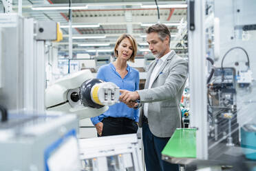 Businessman with tablet and woman talking at assembly robot in a factory - DIGF07881