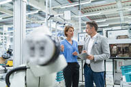 Businessman with tablet and woman talking at assembly robot in a factory - DIGF07884