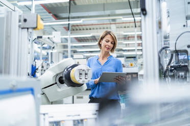 Businesswoman with tablet at assembly robot in a factory - DIGF07890