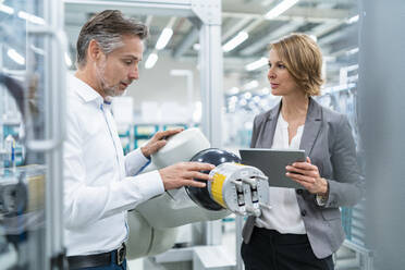 Businesswoman and man talking at assembly robot in a factory - DIGF07896