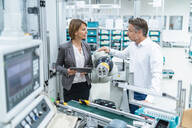 Businesswoman and man talking at assembly robot in a factory - DIGF07899