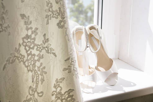 Close-up of wedding sandals by dress on window sill at home - DAWF00901