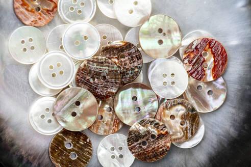 Close-up of buttons made with shells on table in workshop - DAWF00919