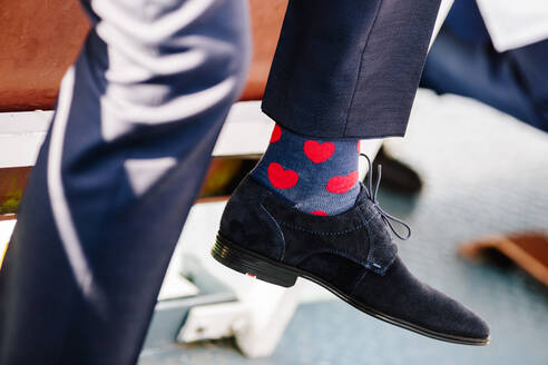 Low section of man wearing socks with heart shape in ceremony - DAWF00949