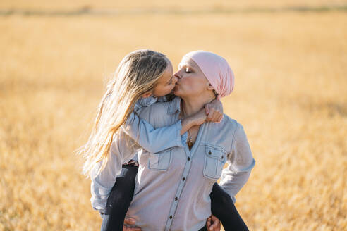 A woman with cancer carrying her daughter on her back, kissing - JCMF00096